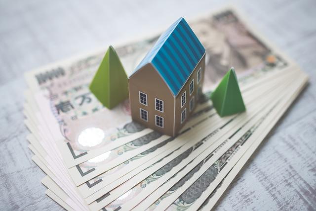 お金の上に乗る家の模型