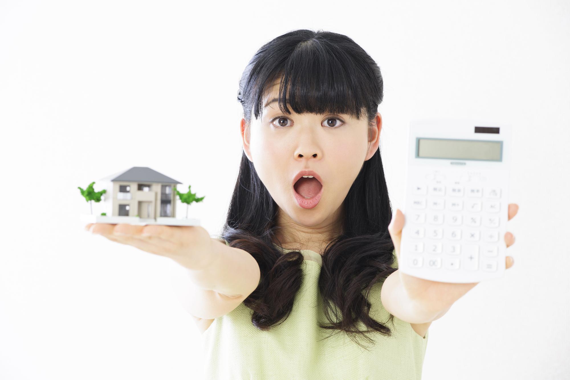 電卓と住宅と女性