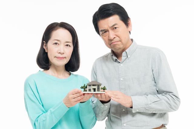 険しい顔で家の模型を持つ夫婦