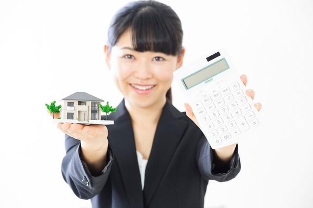 家の模型と電卓を持った女性